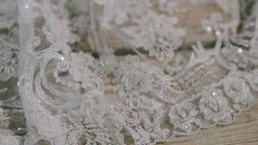 Close-up glijdend schot van detail op de huwelijkskleding die op de houten oppervlakte, prachtige witte kleding voor een bruid li stock footage