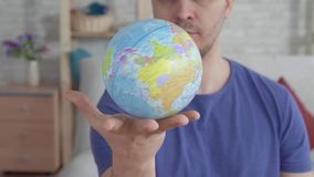 Close up globe spinning in the palm of a man slow mo. Close up small globe spinning in the palm of a man slow mo stock footage