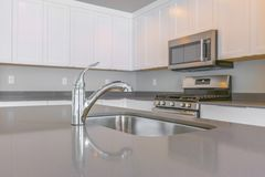 Close up of a glossy countertop with faucet and sink inside a modern kitchen. Cabinets, cooking range, and microwave are installed on the gray wall stock images