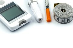 Close up of glucometer with blood sugar test stripe, insulin injection syringes and pills with Measure. Tape,medicine, diabetes, advertisement and health care stock photography
