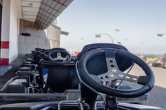 Close up of Go Kart steering wheels. Close up of a go kart steering wheel in a line of parked go karts on a racing track on a cloudless day Stock Images