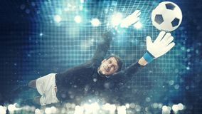 Close up of a goalkeeper dives to save a shot aimed at the goal with light effects. Goalkeeper catches the ball in the stadium during a football game royalty free stock images