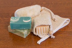 Close Up of Goats Milk Soap on Medium Oak Table. Close up of three bars of goats milk soap with a ramie soap holder, a ramie washcloth and a body scrubber on a stock photos