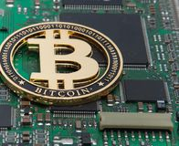 Close-up of gold bit coin, computer circuit board with bitcoin processor and microchips. Electronic currency, internet finance ryp. To currency. Bitcoin mining stock photo