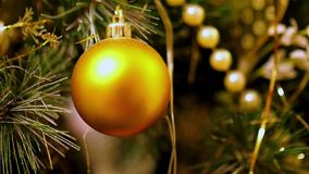 Close-up of gold Christmas balls hanging on artificial fir. Flashing yellow lights Christmas tree garland. stock video