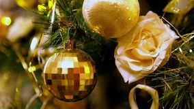 Close-up of gold Christmas balls hanging on artificial fir. Flashing yellow lights Christmas tree garland. stock footage