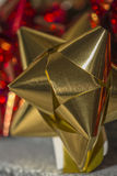 Close up of a gold christmas gift bow. With red bokeh Stock Photo
