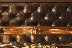 Close-up Gold fabric upholstered headboard with buttons textile background, retro Stylish bedroom furniture with royalty free stock image