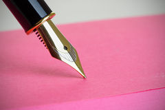 Close up of a Gold Fountain Pen Nib. On a pink note pad, with vignette Stock Photo