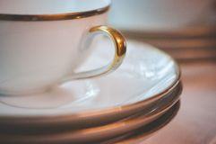 Close up of Gold Rimmed Tea Cup and Saucers. Close up of gold rimmed tea cup handle and saucers indoors on a windowsill stock photography