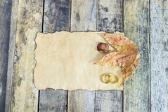 Close up gold ring, dry leaves and old paper on wooden table Stock Photo