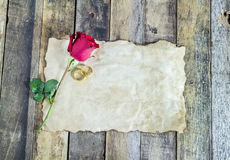 Close up gold ring, red rose and old paper on wooden stock photos
