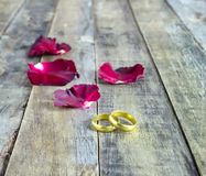 Close up gold Ring and rose petals on a wooden background Stock Photos