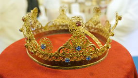 Close up of gold wedding crowns with sapfire, rubin and brilliant prepared for ceremony of marriage in a church. Close up of two gold wedding crowns prepared stock footage