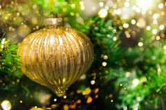 Close up of golden ball ornament hanging on decorated Christmas tree. Sparkling garland bokeh lights glitter. Magic cozy holiday. Atmosphere. Authentic stock image