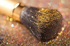 Close-up on golden brush and shining powder Stock Photo