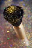 Close-up on golden brush and shining powder Royalty Free Stock Photos