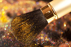 Close-up on golden brush and shining powder Stock Image