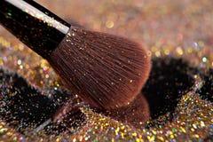 Close-up on golden brush and shining powder Stock Photos