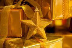 Close-up of golden Christmas star and gifts piled up in stack blurred Royalty Free Stock Image