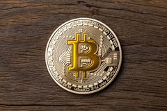 Close up of golden cryptocurrency yellow bitcoin on wooden backg. Round. High resolution photo Royalty Free Stock Images
