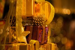 Close-up of golden gifts piled up in stack blurred in gold bokeh background - selective focus. Royalty Free Stock Photos