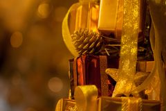 Close-up of golden gifts piled up in stack blurred in gold bokeh background - selective focus Royalty Free Stock Photo