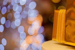 Close-up of golden gifts piled up in stack blurred in gold bokeh background - selective focus. Royalty Free Stock Images