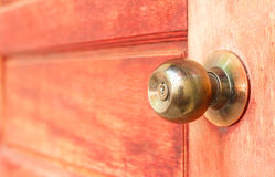 Close up golden knob on red wooden door background Royalty Free Stock Image