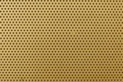 Close up on a golden metalic sheet texture with small holes stock image