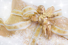 Close up of golden present box with angel playing violin for chr Stock Image