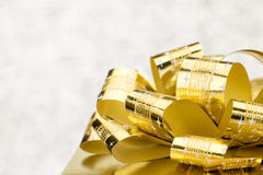Close up Golden present box with big bow at bokeh white blur background Royalty Free Stock Photo