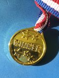 Close-up of winnier golden medal. Close-up of golden shinning winning medal with colorful ribbon royalty free stock images