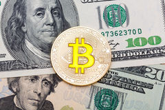 Close up of golden yellow bitcoin on US dollars background. High resolution photo Royalty Free Stock Image
