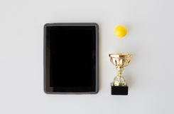 Close up of golf ball, cup and tablet pc Royalty Free Stock Photo