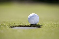 Close-up of a golf ball on the edge of a hole Stock Images