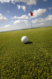 Close up of golf ball on green with flag in background Stock Photos