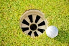 Close-up of golf ball near hole Royalty Free Stock Photo