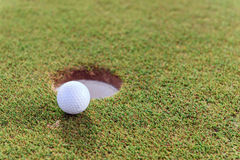 Close up of golf ball near hole Royalty Free Stock Photos