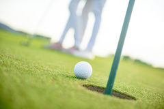 Close up of golf ball next to hole. Golf ball on lip of cup. Close up of golf ball going to fall in hole with couple of golfers background stock images