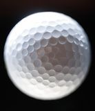 Close-up of a golf ball over dark background Royalty Free Stock Image