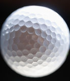 Close-up of a golf ball over dark background Stock Photo