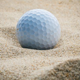 Close up golf ball in sand bunker shallow depth of field. A golf. Ball plugged deep in sand trap Stock Photography