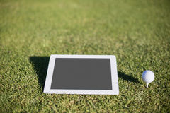 Close-up of golf ball on tee by digital tablet royalty free stock image