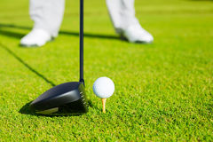 Close up of Golf Ball on Tee. Golf Ball on Tee, Man about to Hit Ball with Driver Stock Image