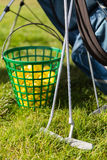 Close up of golf club and balls in basket on grass Royalty Free Stock Photo