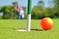Close up golf hole and a ball on green grass golf course. Stock Images