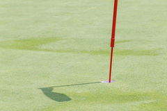 Close up golf hole with flagpole on green grass and its shadow i Stock Photography