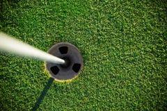 Close-up of golf hole. Close-up of golf hole with white flag rod stock image
