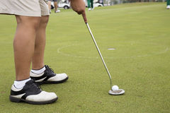 Close up Golf player putting ball. In to hole Stock Photo